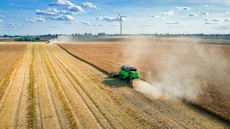 Harvester on field and wind turbine on background, aerial view Foto de archivo - 130454116