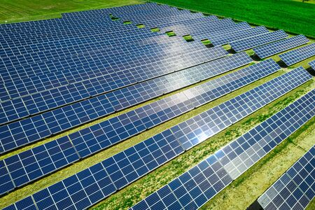 Solar panels on green field with blue sky, aerial view Imagens