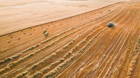 Aerial view of tractor with round hay on field 写真素材