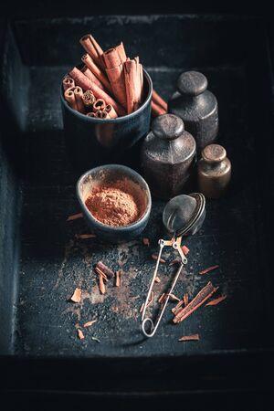 Heap of cinnamon sticks on a dark background