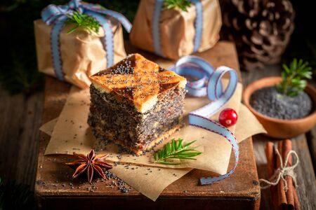 Closeup of poppy seed cake for Christmas on wooden table Фото со стока