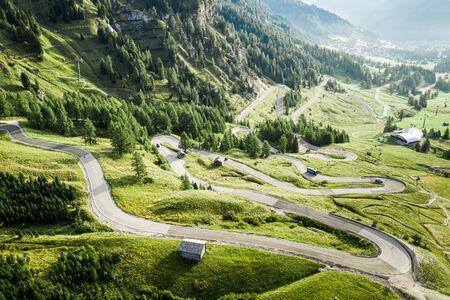Serpentine and green hills in Passo Gardena, Dolomites, aerial view Stok Fotoğraf