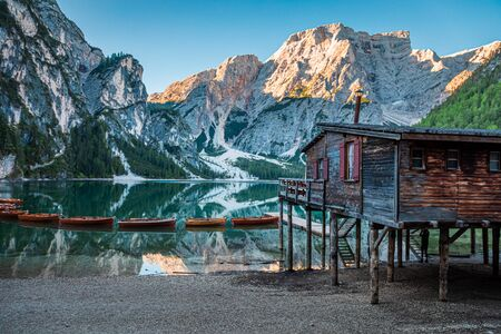Famous Lago di Braies and wooden hut at sunrise, Dolomites