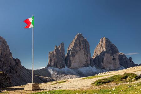 Italian flag and Tre Cime di Lavaredo at sunrise, Dolomites