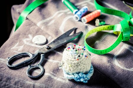 Closeup of sewing threads, scissors, cloth and tape measure Archivio Fotografico