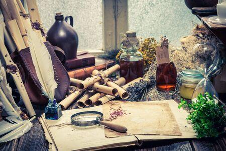 Taller rústico de brujas con rollos antiguos y plantas.