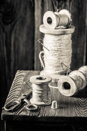 Table with scissors, needle and threads in tailor workshop