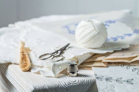 Thread, scissors and homemade white embroidered napkins