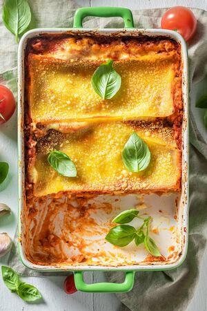 Homemade lasagna with bechamel sauce, tomatoes and herbs Фото со стока