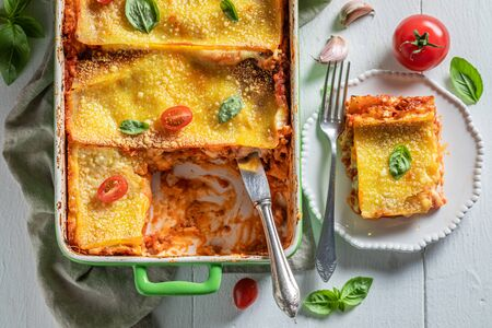 Spicy lasagna with bechamel sauce, tomatoes and herbs Фото со стока