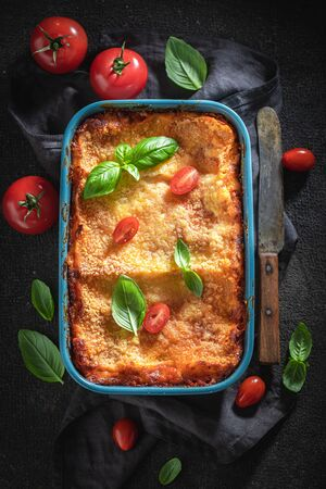 Hot lasagna with bechamel sauce, tomatoes and herbs