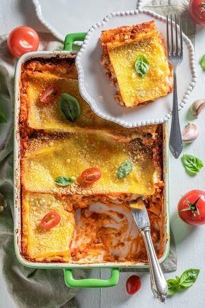 Hot lasagna with basil, tomatoes and parmesan Фото со стока - 133464144