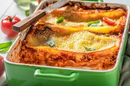 Spicy lasagna baked in casserole with cheese Фото со стока