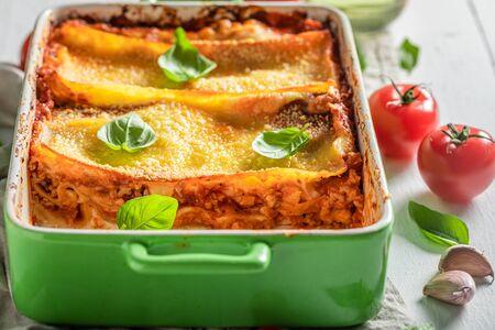Tasty lasagna with basil, tomatoes and parmesan