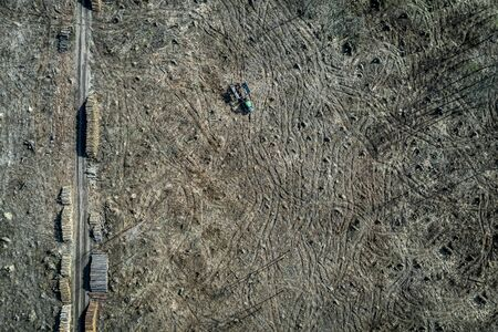 Small tractor in the middle of deforestation forest, aerial view