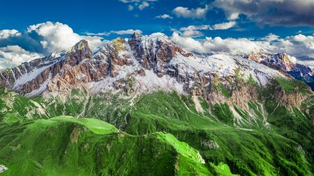 Passo Giau and green hills in Dolomites, aerial view