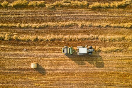 Top down view of tractor collecting and pressing hay