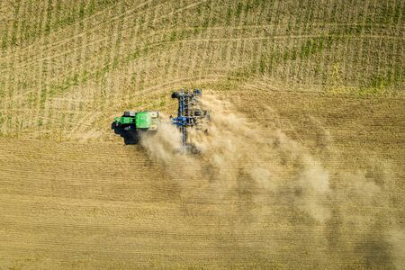 Top down view of tractor plowing dry field, aerial view
