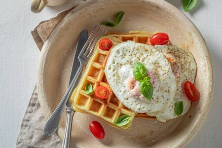 Homemade waffles with tomatoes, fried eggs and basil
