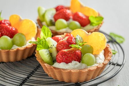 Freshly baked mini tart with mix of fruits and cream