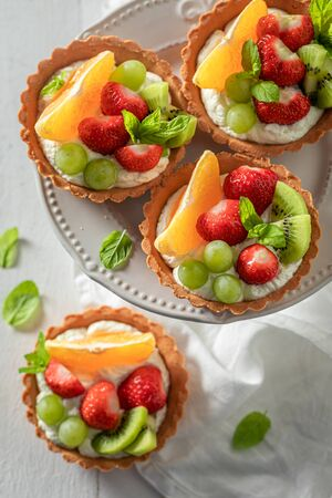 Top view of mini tart with fruits and cream