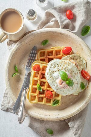 Tasty waffles with tomatoes, fried eggs and basil Stock Photo