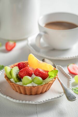 Delicious mini tart with mix of fruits and cream