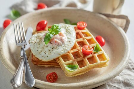 Fresh waffles with fried eggs and cherry tomatoes