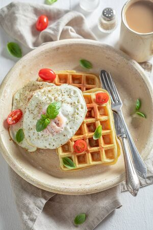 Delicious waffles with tomatoes, fried eggs and basil