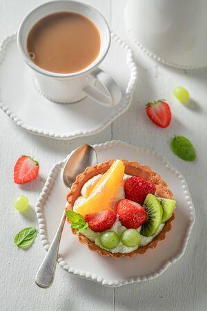 Fresh mini tart with fresh fruits, mint and whipped cream