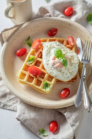 Tasty waffles with fried eggs and cherry tomatoes