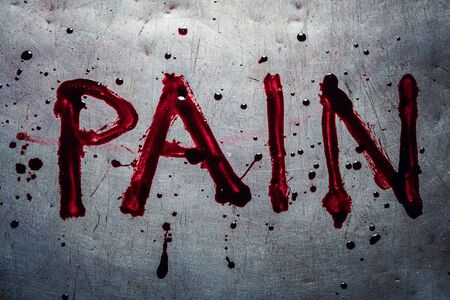 The word pain painted by blood on a metal table Фото со стока