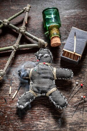 Creepy voodoo doll pierced by a needle as harming