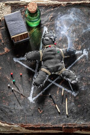 Vintage voodoo doll pierced by a needle as harming Фото со стока