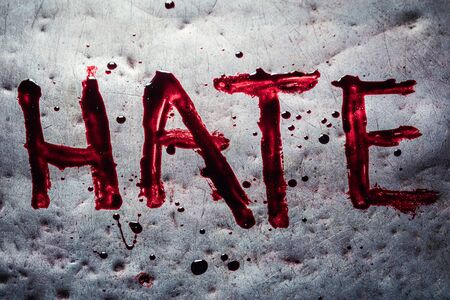The word hate painted by blood on a metal table