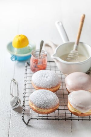 Homemade donuts with white icing on white table