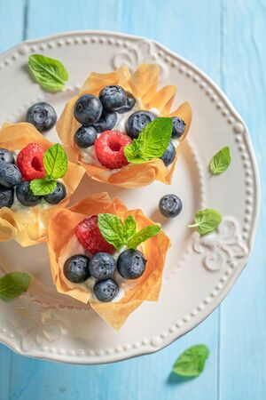 Freshly baked phyllo cups with fresh berries and whipped cream
