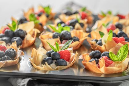 Freshly baked phyllo cups with blueberries, raspberries and whipped cream