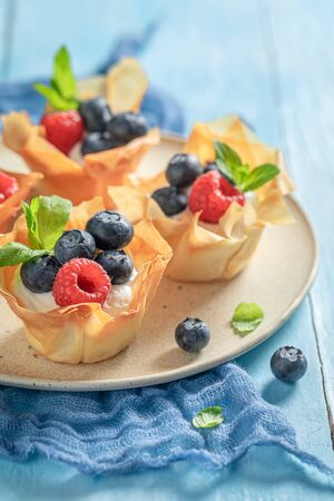 Homemade phyllo cups made of berry fruits and cream