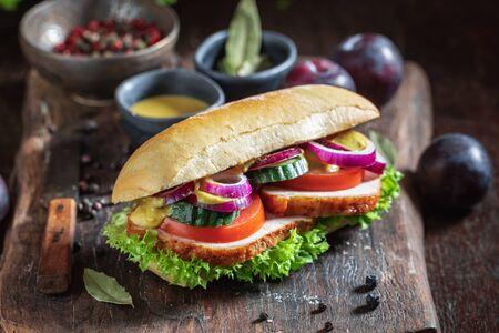 Frisches Sandwich mit gebratenem Schweinenacken, Gurke und Zwiebel