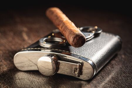 One cigar on leather hip-flask on wooden table