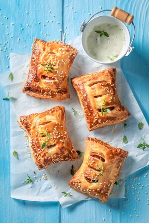 Top view of tasty sausage roll with thyme and sesame