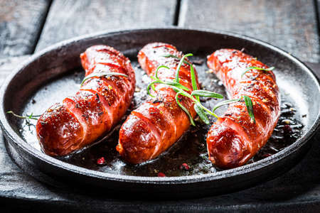 Closeup of roasted sausage with herbs and pepper