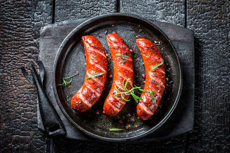 Top view of roasted sausage with fresh herbs