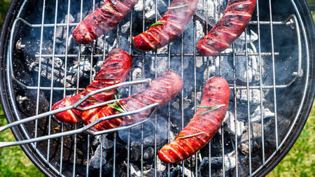 Top view of sausages on garden grill in summer