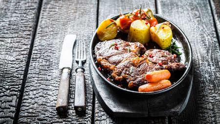 Roasted steak with vegetables on burned table 版權商用圖片