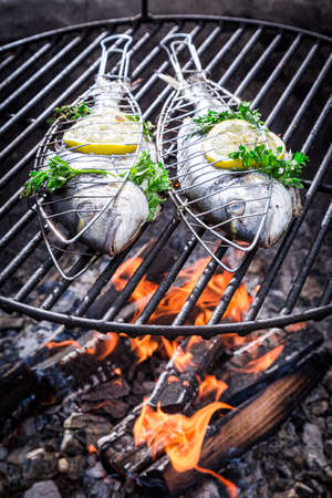 Fish with lemon and herbs on grill with fire