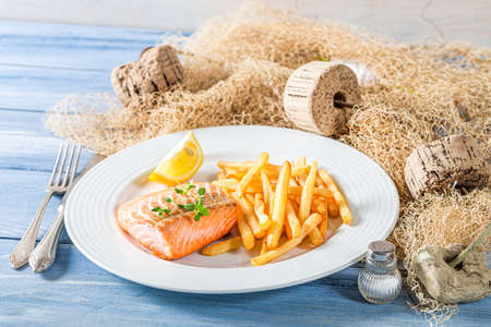 Closeup of french fries with salmon on blue table 版權商用圖片