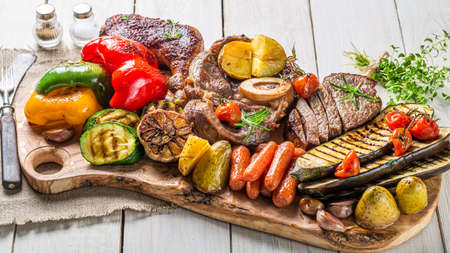 Grilled vegetables and meat with herbs on white table