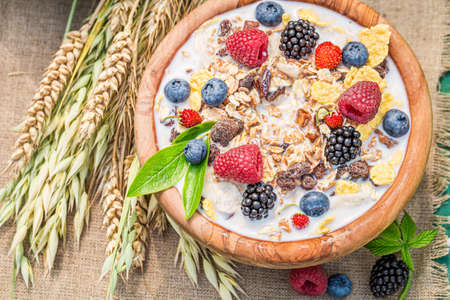 Top view of granola with berry fruits and milk